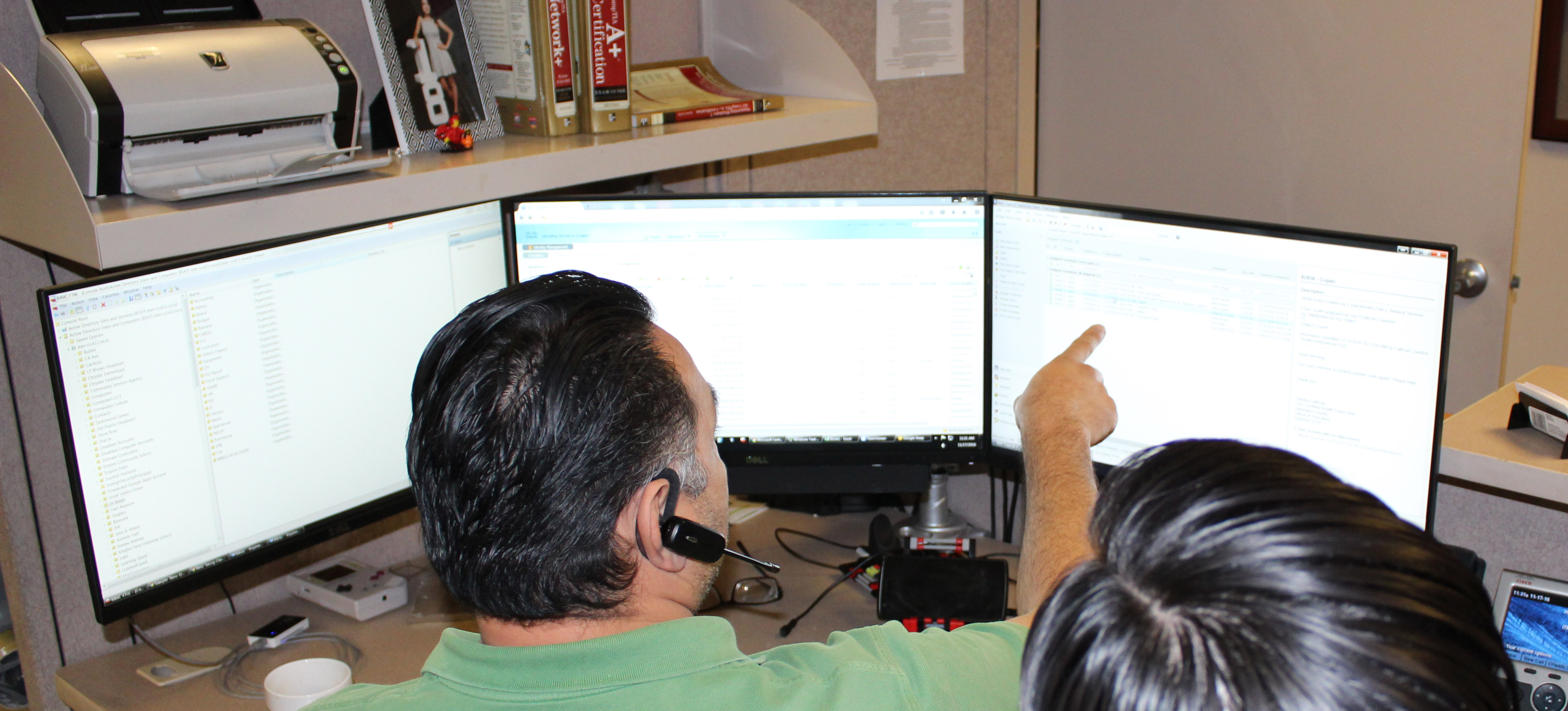 help desk employees pointing at a screen