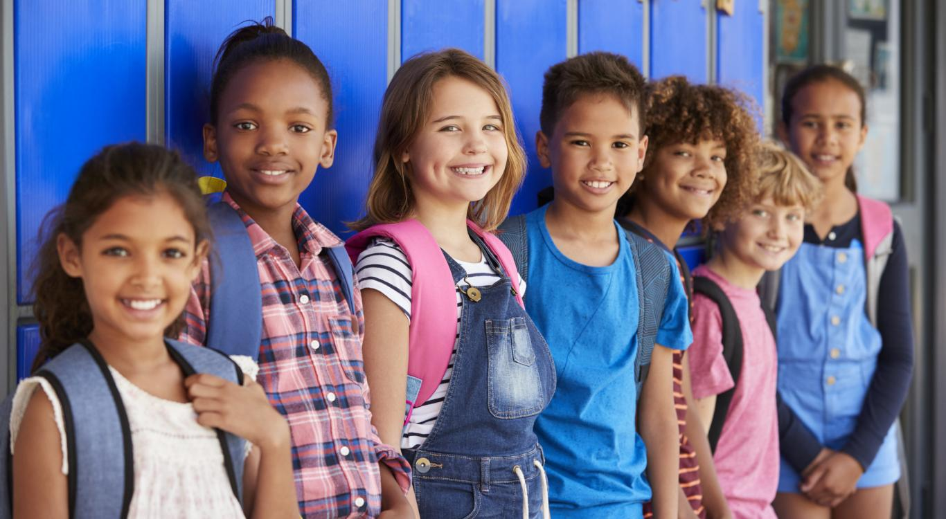 elementary students standing in front of lockers