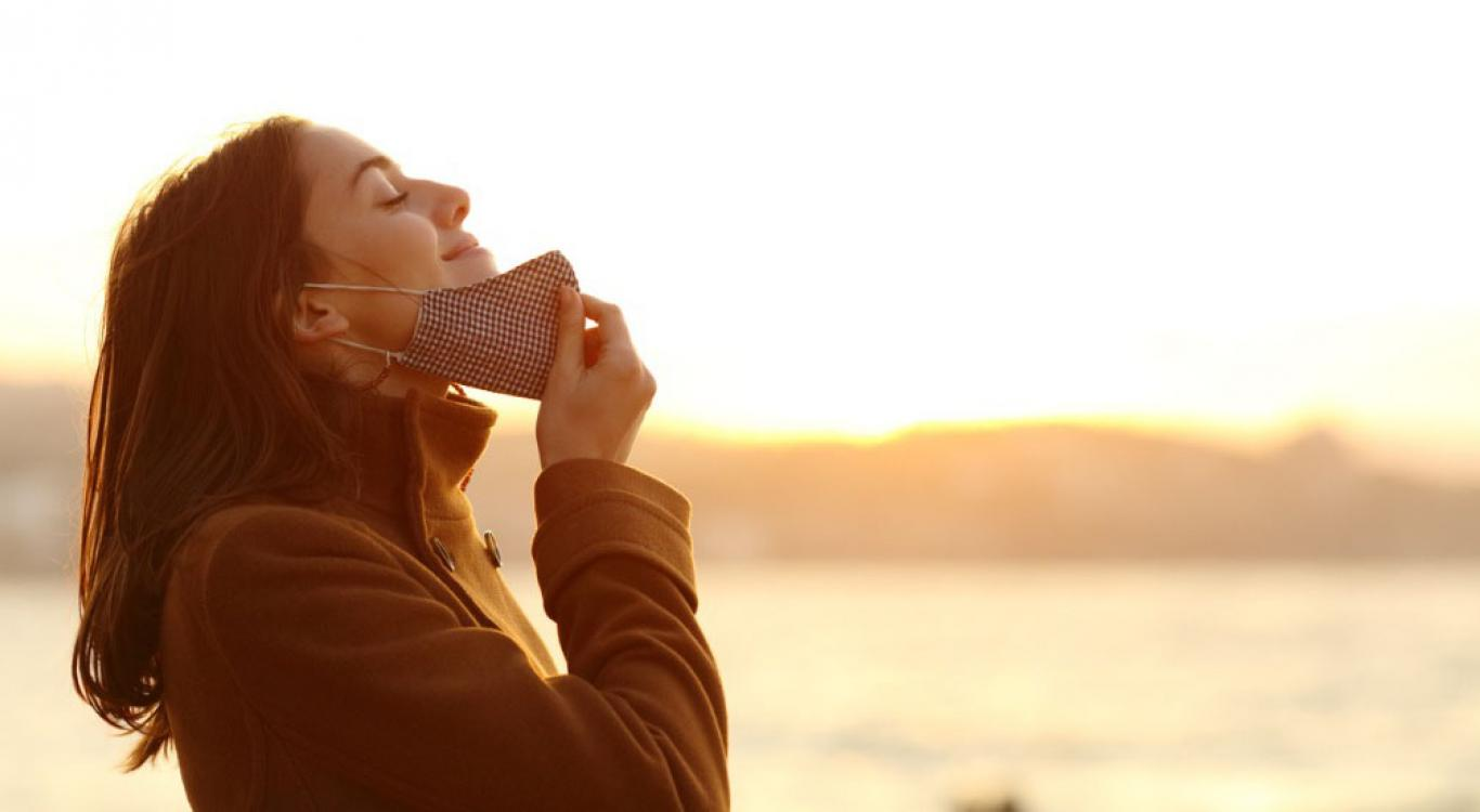 woman breathing outside holding mask away from face