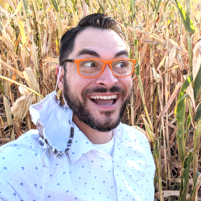 Brandon Schut, smiling, whilst in a corn field