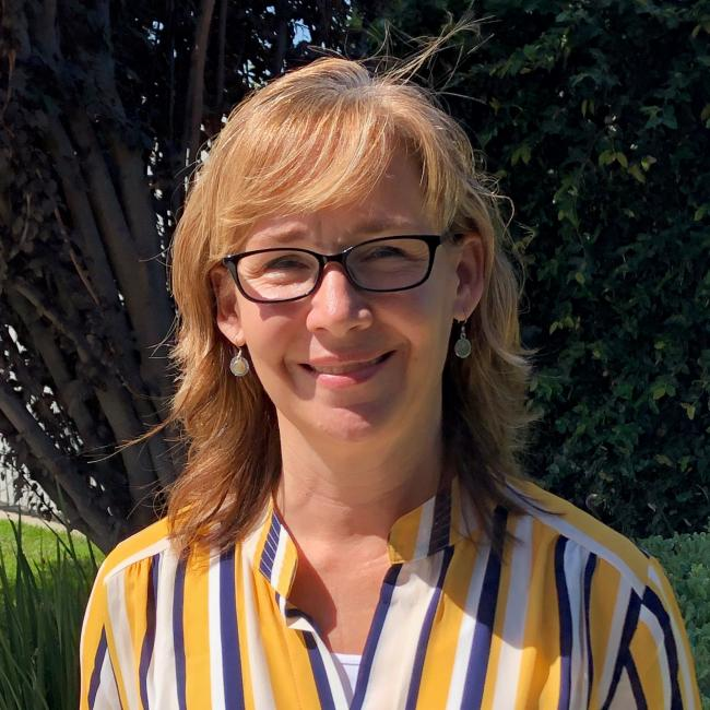 headshot of Christine Sisco in front of a shrub wearing a striped shirt.