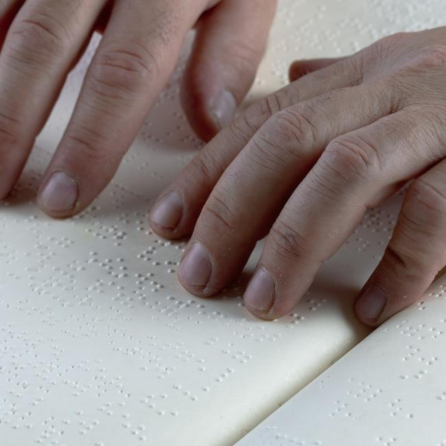 hands going over pages of braille text