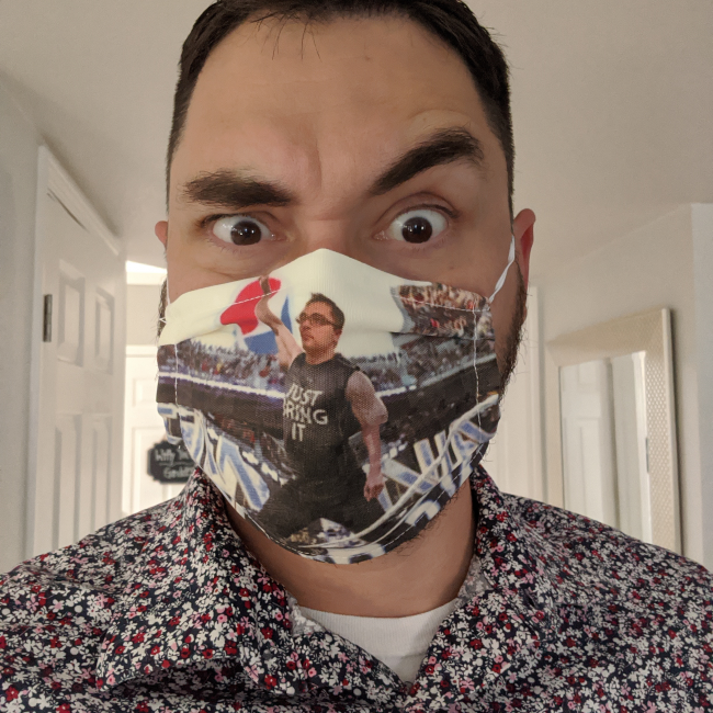 """a headshot of Brandon Matthew Schut wearing a face mask with his head photoshopeed onto a photo of the Rock at Wrestlemania. Brandon is also wearing a floral print shirt, which he says, """"has a lot of drip."""""""