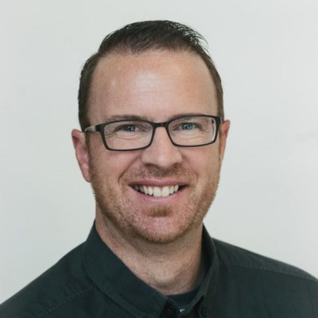 headshot of Gregg Eilers, wearing a black button-up shirt