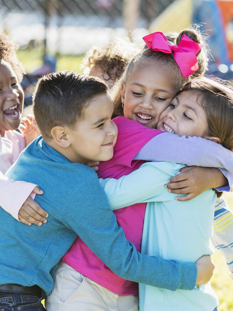 Four preschool children hugging