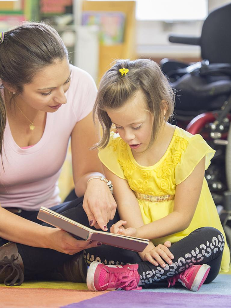 Teacher with girl near wheelchair