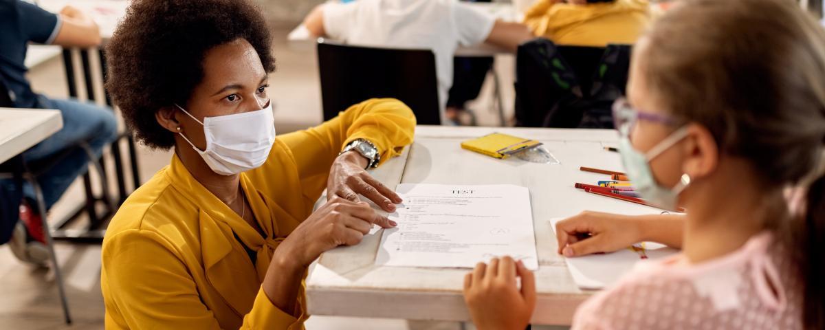 teacher helping student at desk wearing masks