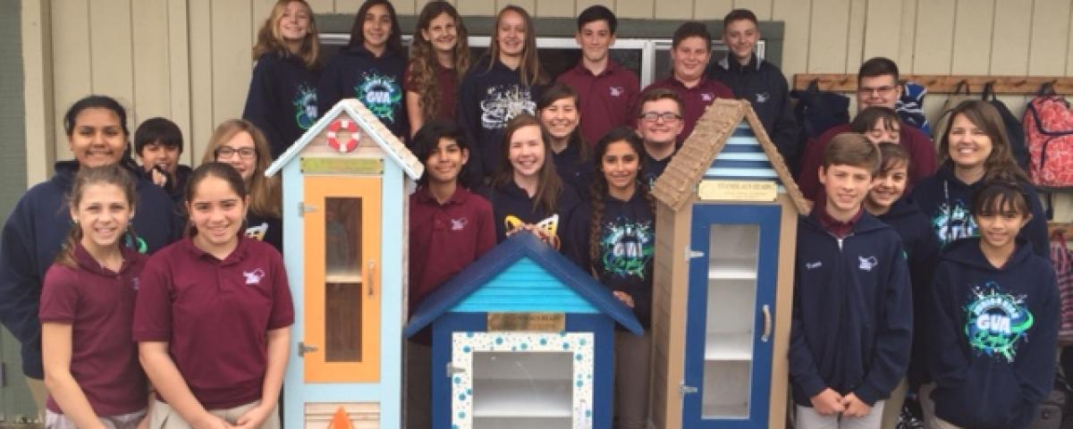 Kids and their painted Little Free Libraries
