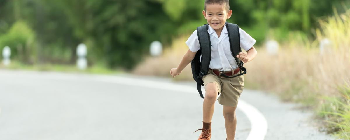 Happy boy running to school.
