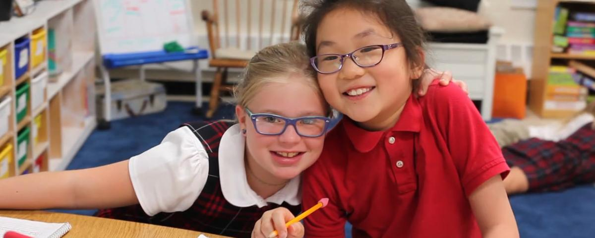 Caucasian and Asian girls with glasses, working on a school project at their desk